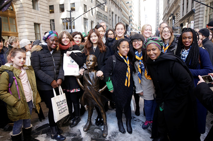 UN Women Executive Director Phumzile Mlambo-Ngcuka meets with young women and girl activists at the Fearless Girl statue on Wall Street. Photo: UN Women/Ryan Brown L-R: Unami Moatswi; Daniela Zelaya; Ashken Aslikyan; Joyce Lee Boram and Heejin Lim (World YWCA); Candela Gonzalez; Zoelisoa Rakotomanana; Danae Fredes-Toledo; Emma Guthrie; Anna Spencer and Jean-Ann Ndow (WAGGGS); with UN Women Executive Director Phumzile Mlambo-Ngcuka at the Fearless Girl statue on Wall Street. Photo: UN Women/Ryan Brown