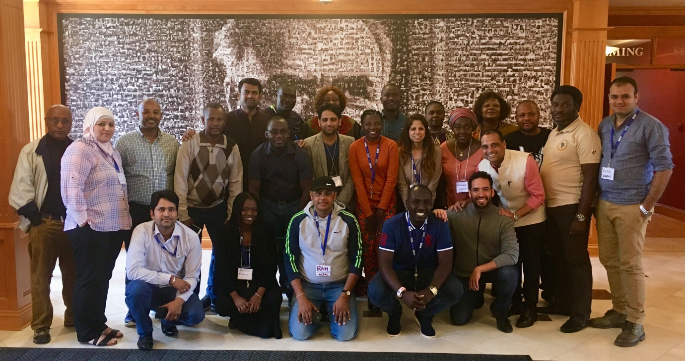 "2018 Livelihoods and Markets participants and one of their facilitators; Yogesh, (bending, third from right), posing in front of  the gallery of pictures of men that contributed at Coady (""The Mosaic of 3479 people'')."